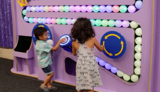 two children adding an orb to a panel in Emotions at Play exhibit